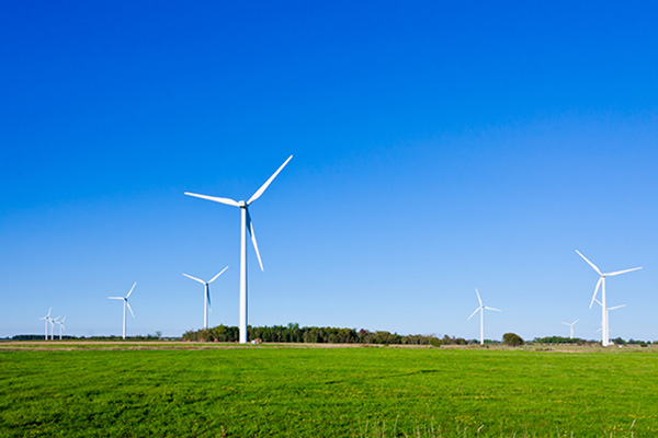 Wind turbine on green grass background