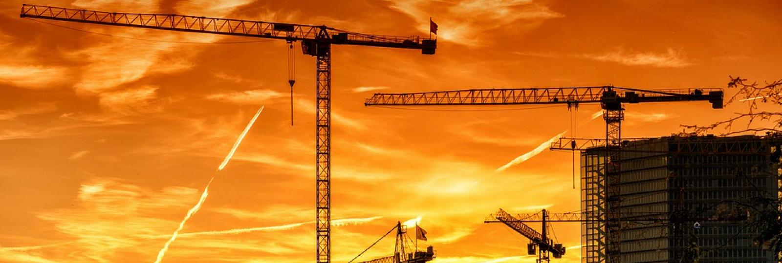 orange sky with cranes construction